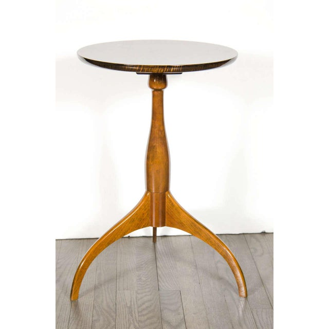 This very sophisticated table features a tripod base with a tapered cylindrical support and a round top in bookmatched...