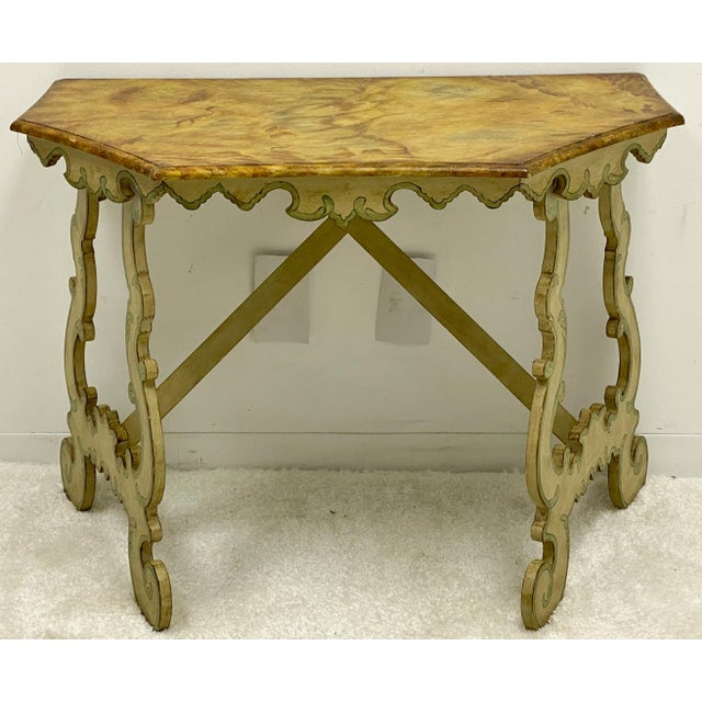 This is a carved wood venetian style painted console table with faux marble top. It is marked with the Chelsea House label...