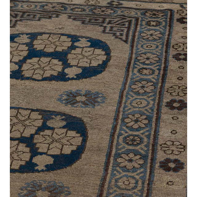 This traditional Khotan runner features a buff-brown field with a column of three royal-blue roundels, each containing...