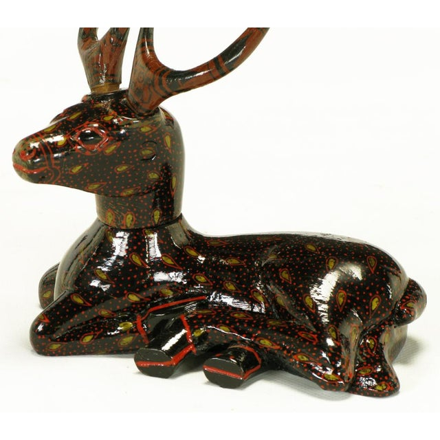 Hand carved wood recumbent deer with large horns and articulated head. Hand painted in a black lacquer with red dots and...