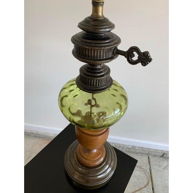 Vintage Hepplewhite carved wood urn, cast metal, and green depression glass table lamp with adjustable burlap shade.