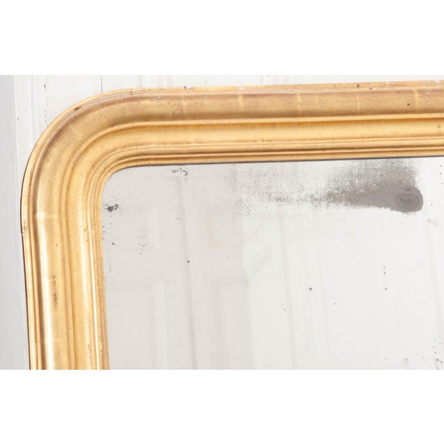A generously proportioned gold giltwood Louis Philippe mirror from 19th century, France. The classically-formed mirror has...