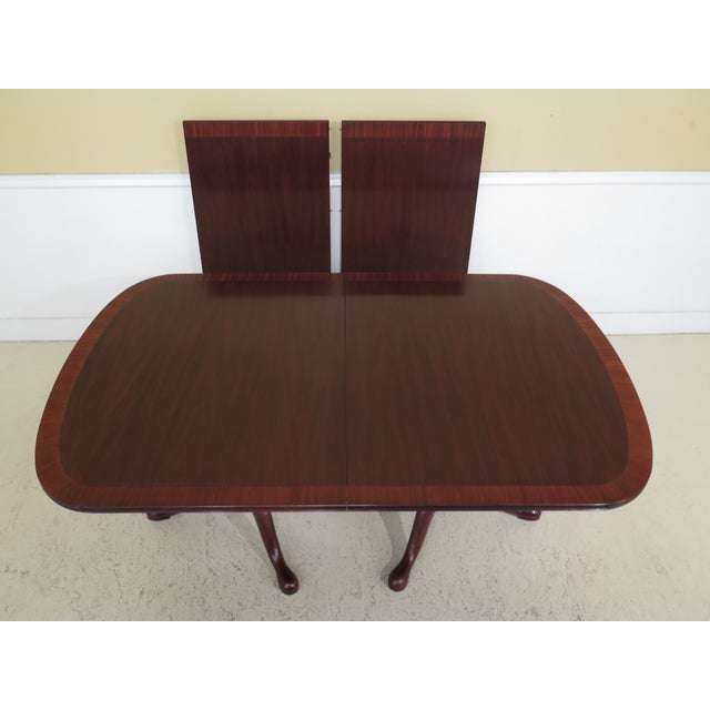 Henkel Harrisbanded mahogany dining room table. Model 2272. Features #29 finish, high quality construction, Queen Anne...