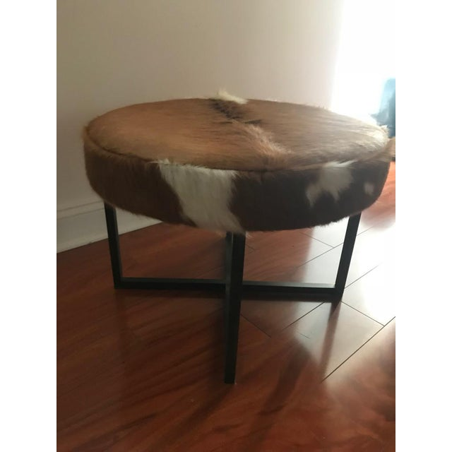 A round upholstered bench having cowhide supported on bronze washed metal base.