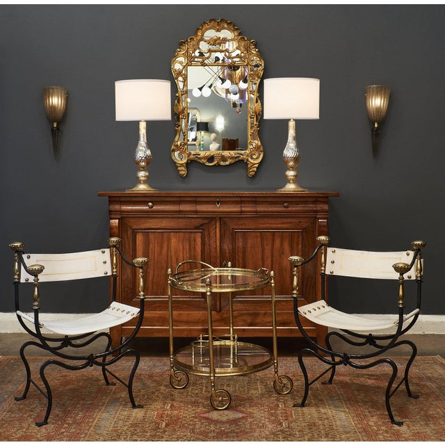A rare and important set of eight Italian Renaissance style armchairs of hand-hammered iron featuring gilt embossed...