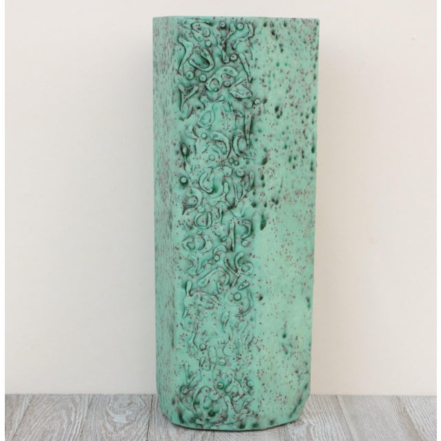 This tall, hexagon-shaped cylinder vase is covered with a heavily textured speckled lava glaze finish and an abstract hand...