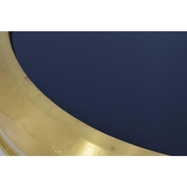 The Carnaby round cocktail table by Bernhardt has a metal base in a patinated gold leaf brass finish and an inset tempered...