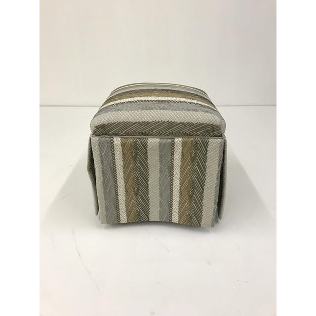 TheDorothy Ottoman is a first quality market sample that comes in a striped fabric. It features a Kick Pleat Skirt and a...