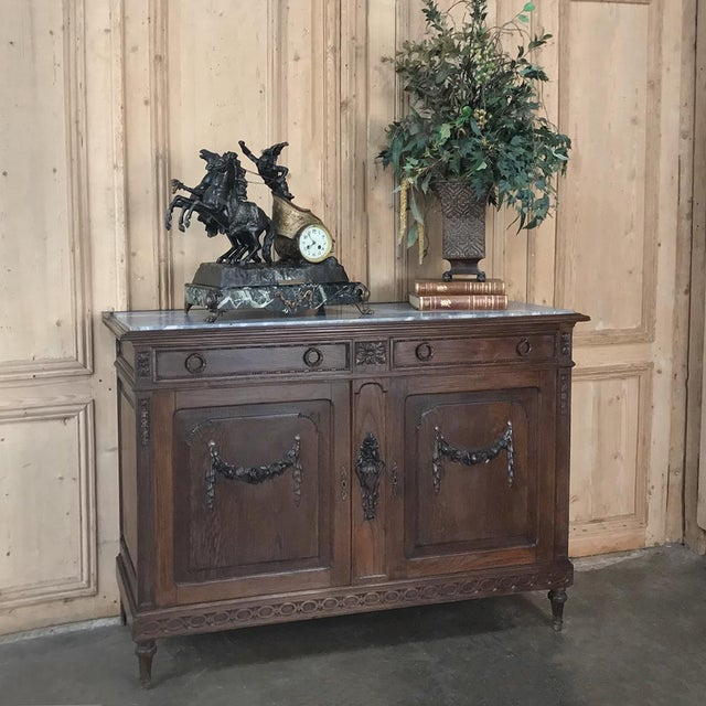 Antique French Louis XVI Marble Top Buffet was rendered from solid oak, and features classical urns with flowers, floral...