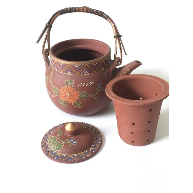 Clay teapot with a beautiful enameled floral design, There are no cracks or chips ,the teapot is in perfect condition. The...