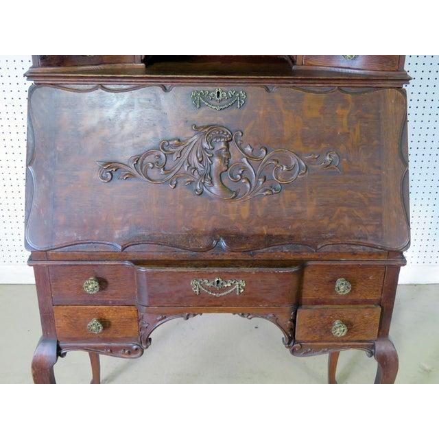 Antique oak Louis XVI style secretary desk with a beveled mirror backsplash and brass accents.