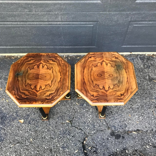 A pair of side tables with walnut veneer top and bottom, and ebonized column posts. Tables have an octagonal shape....