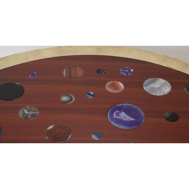 A monumental Italian coffee table with multi-color agates inlaid in a Sapelle wood top with cylindrical brass legs and...
