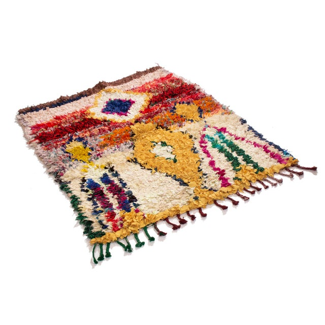 Originating from Morocco in 1950, this vintage midcentury Moroccan fabric rug has a unique grasp of dimensionality. Hand...