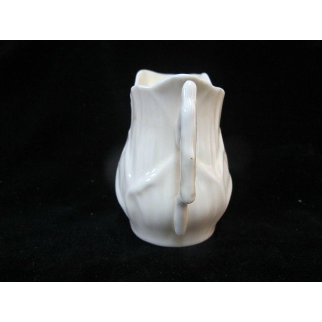 """Beautiful Belleek porcelain creamer pitcher, white with lily design. Measures 3 1/2"""" x 3 1/4"""". Black 3rd mark at base...."""