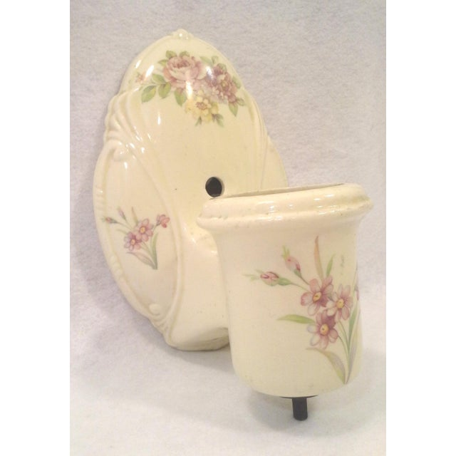 A charming ceramic wall light in ivory colored ceramic with a pink floral design. This vintage sconce has an integrated...
