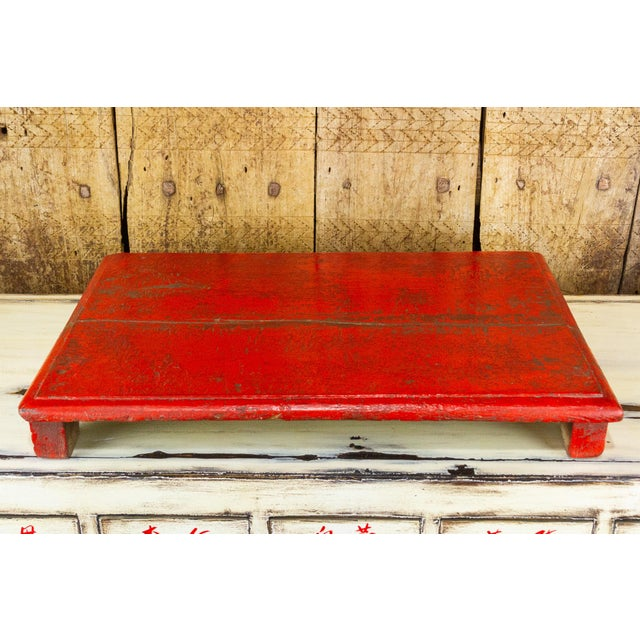 A traditional and low bajot table with a vibrant red finish. Bajot tables are traditionally used in India for spiritual...