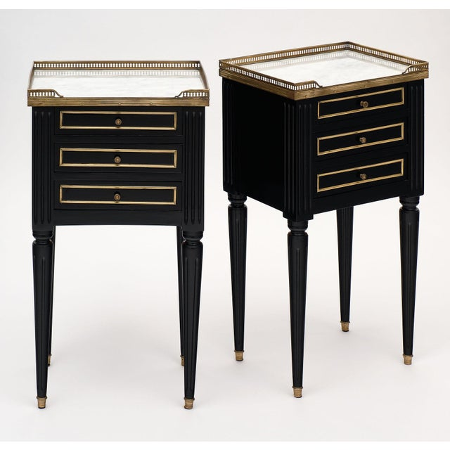 Antique Louis XVI style side tables made of mahogany and finished with a lustrous French ebony polish. Both tables have a...