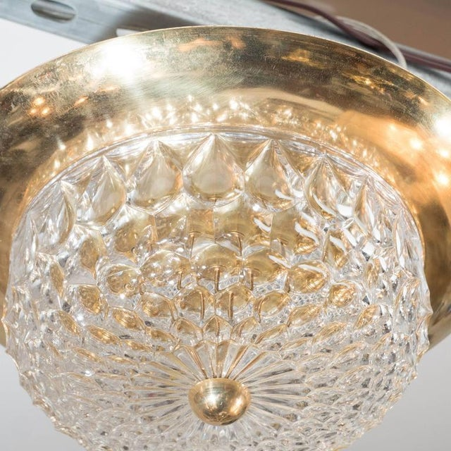 A Mid-Century Modernist flush mount chandelier with polished brass fittings. A diamond shape faceted crystal dome is...
