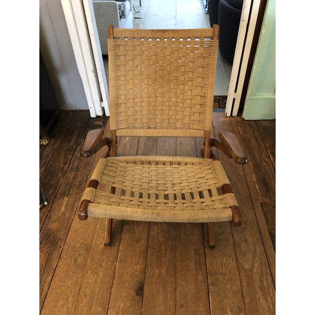 An ingeniously designed mid century modern woven rope chair having a low slung silhouette, handsome sleek wood arms and...