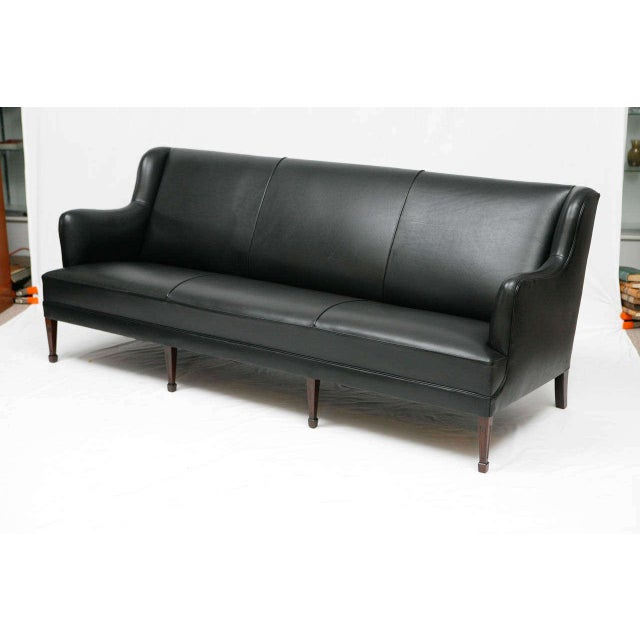 Black leather sofa designed by Frits Henningsen. Store formerly known as ARTFUL DODGER INC