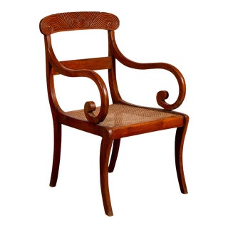 Antique Javanese Wooden Armchair with Carved Back, Curving Arms and Rattan Seat For Sale