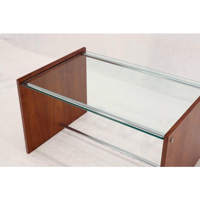 Compact Mid-Century Modern rosewood and chrome base rectangular coffee side table. This item includes restricted materials...