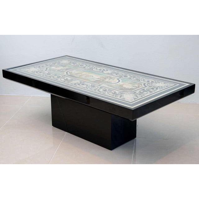 A fine scagliola top with central landscape and figures inset within a black lacquer low table.