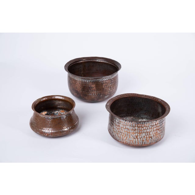 Set of three Indian hand wrought copper vessels. The nickel silver wash over copper highlights the hammered vessels...