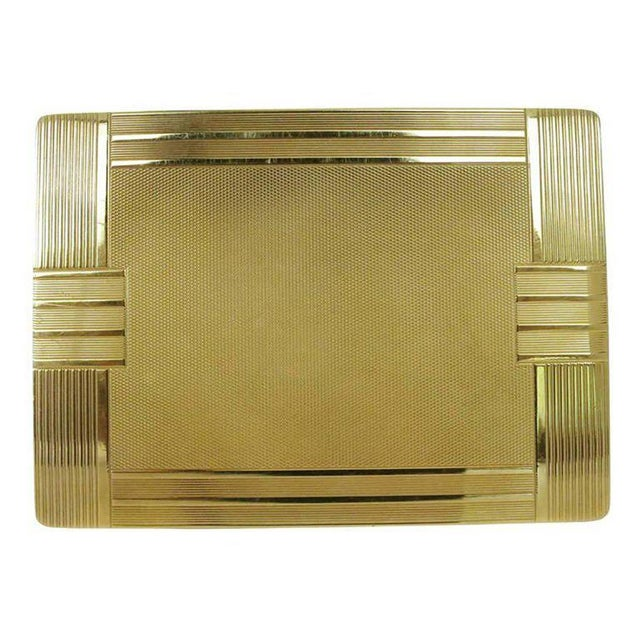 A solid 18-karat gold case with geometric Art Deco lines, this cigarette case has lines textured along the exterior and is...
