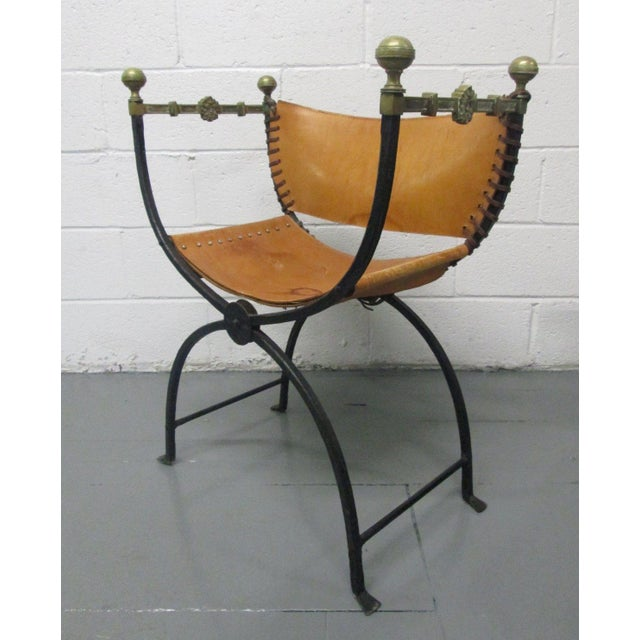 The chair has a wrought iron frame, leather seat / back and the chair folds.