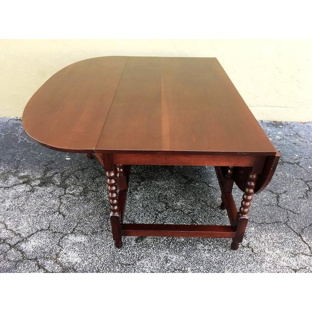 About American Sheraton cherry table with a one board top, two scalloped drop leaves consisting of one board, interior...