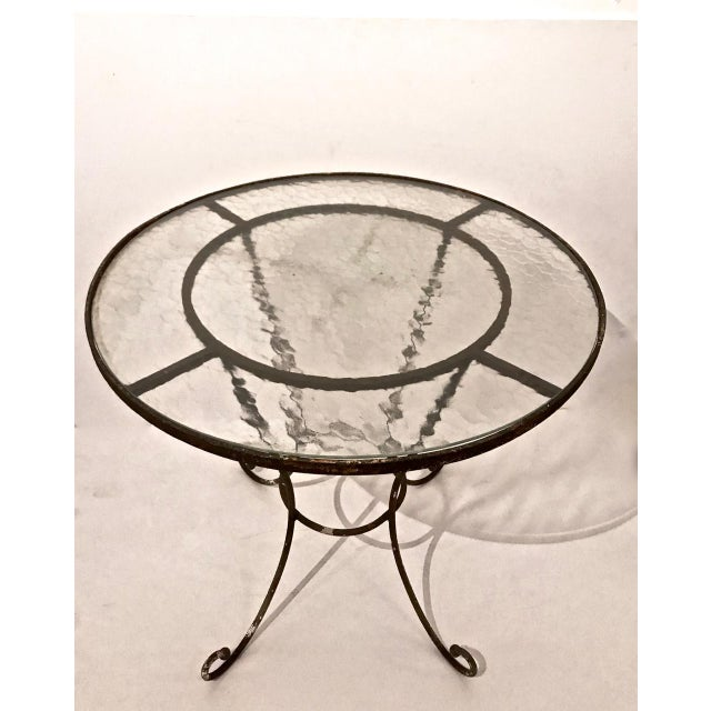 This is a beautifully patinated French iron bistro table. The little brass ball finials at the tips of the legs are its...