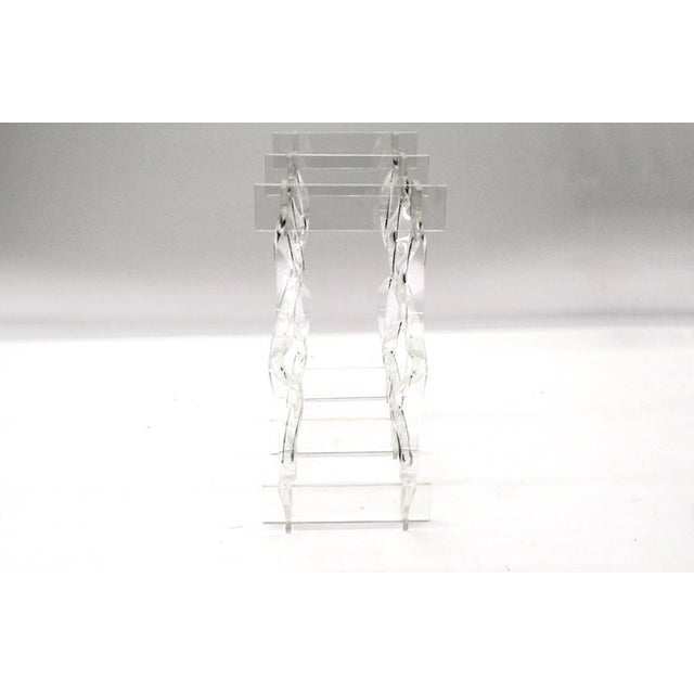 Mid century modern style clear acrylic tabletop wine rack. The acrylic rack features space for eight bottles to rest in a...