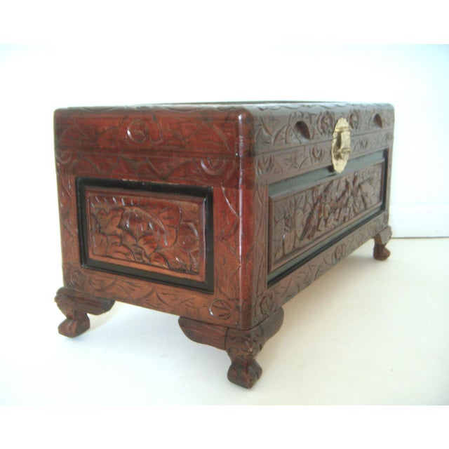Highly carved oriental/Asian chest on four legs with brass hardware - lock, plate and hinges. The storage area is...