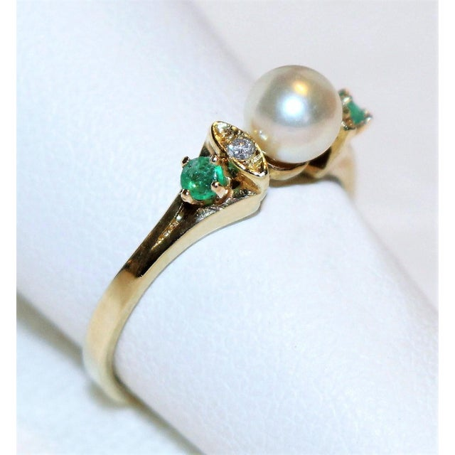 Dainty 14k gold ring set with a 5mm cultured pearl and embellished on either side with small prong set diamonds and...