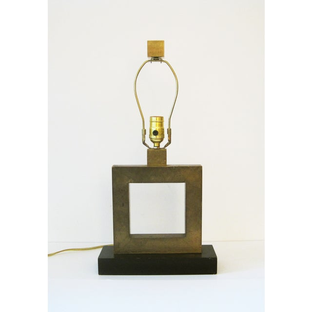 Square, burnished brass table lamp on a black, wood base with a matching, square brass finial. By Robert Abbey. To top of...