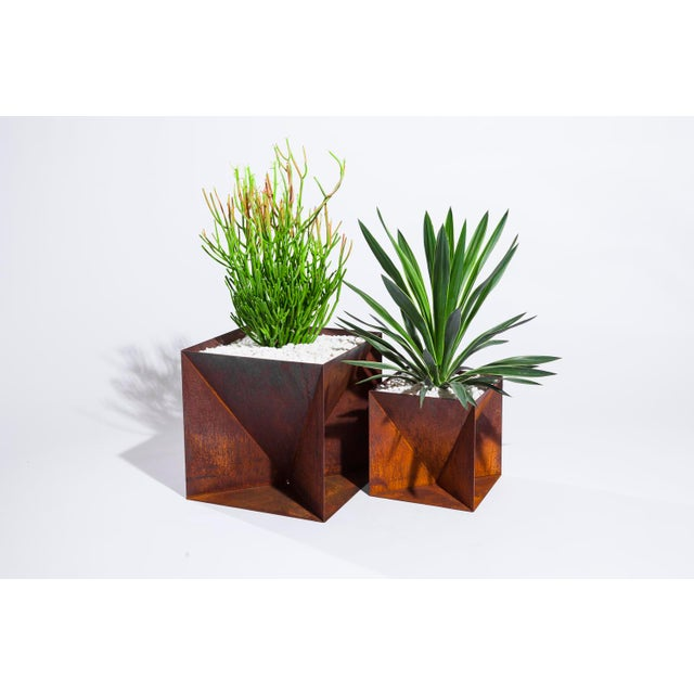 The Steel Origami Planter is an outdoor planter made from weathering steel that will develop a warm rich patina in time....