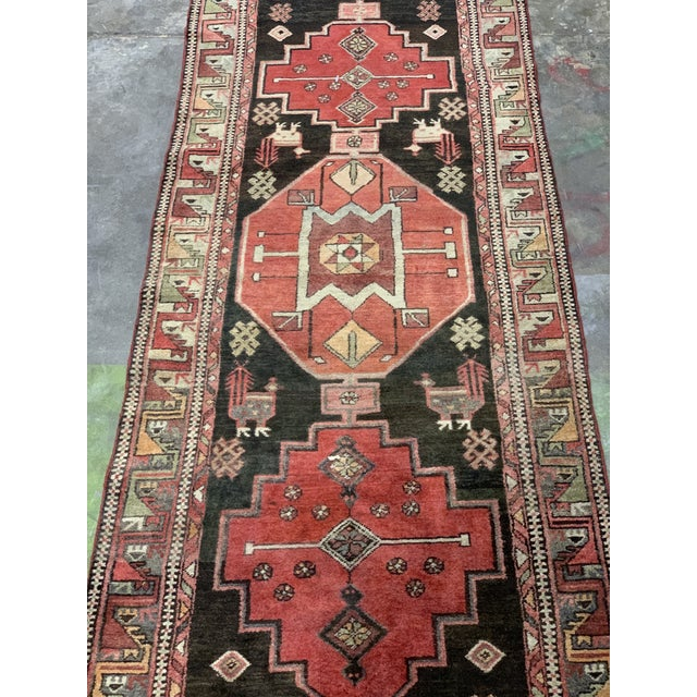 This is a vintage Persian runner rug. The piece was made in the 1950s.