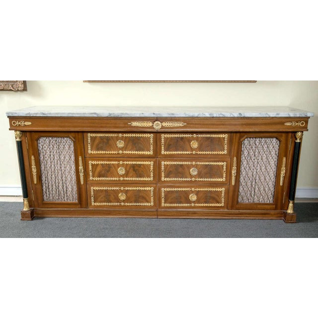 This impressive, Empire-style sideboard features two separate commodes on either side, each with three drawers and grilled...