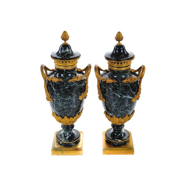"A stunning pair of 19th c. French black marble gilt bronze urns c.1860s. They are large and measure 18"" tall. These..."