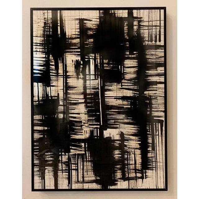 Set of 2 black and white abstract ink paintings on paper. Framed in a modern black metal frame. Each painting measures 18...