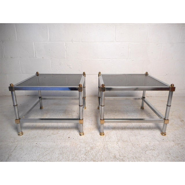 Stylish pair of Regency two-tier side tables. Polished chrome frame with brass accents with smoked glass surfaces. Please...