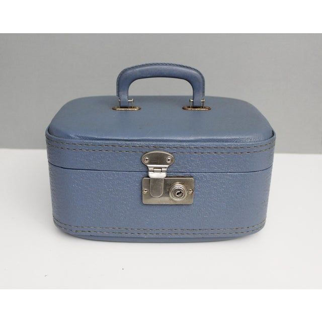 Vintage blue hardshell vinyl train case. Large roomy interior lined in fabric. The inside of the lid has 2 elastic bands...