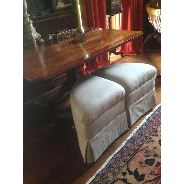 Pair of crescent-shaped ottomans on brass casters newly upholstered in Belgium linen to be used as pull-up extra seating...