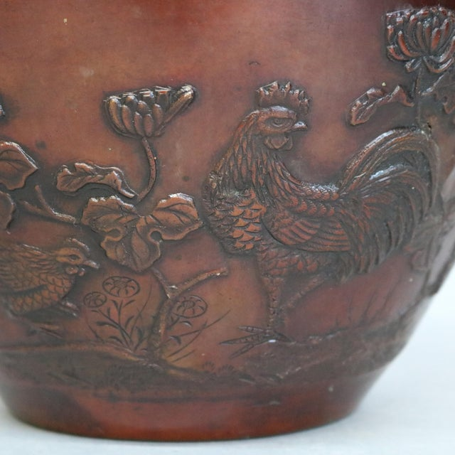 An antique Japanese jardinière offers bronze construction having embossed garden scene with birds and flowers, circa 1920....