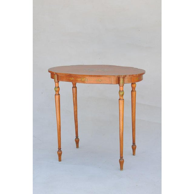 Oval table, of satinwood, having freeform shape top with exquisite handpainted floral details, apron with fluting and...