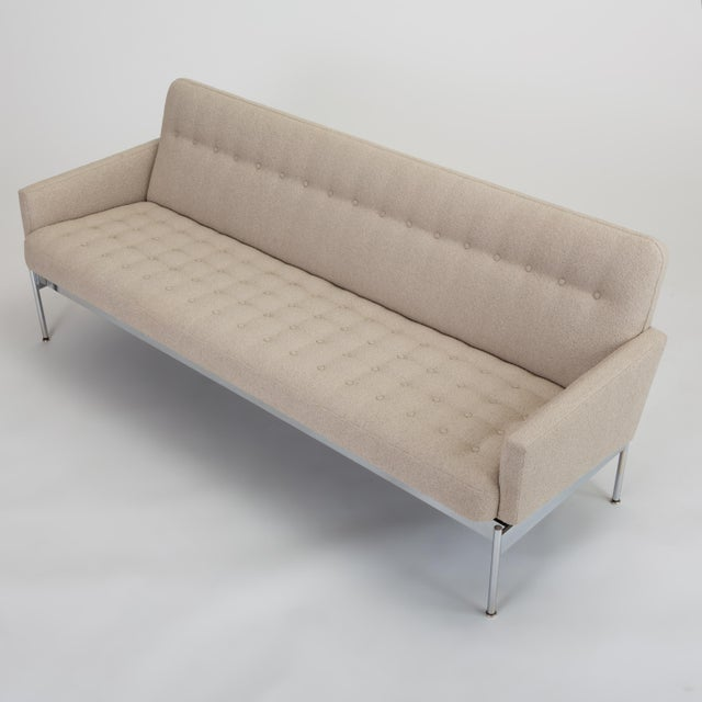 A mid century modern sofa with a slender profile sits atop a chrome base. The integrated cushion is button tufted, and a...