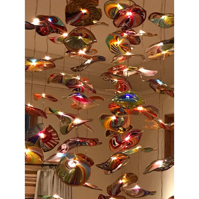 "There is a heavy 36"" brass base with LED lights; 15 strands of lights, each with 4, 5 or 6 hand blown glass disks of 6""-7""..."