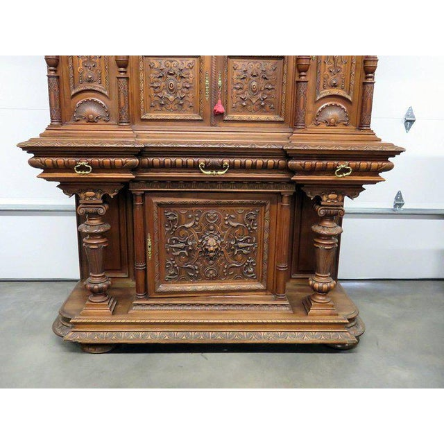 Renaissance style carved cupboard with three drawers, four doors and three shelves.